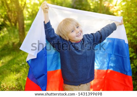 Portrait of cute little boy in public summer park with russian flag on background. Fans child supporting and cheering their national team. Day of independence. Pride and patriotism. #1431399698