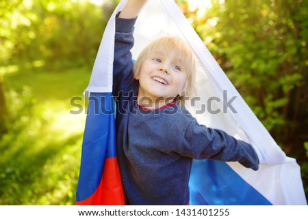 Portrait of cute little boy in public summer park with russian flag on background. Fans child supporting and cheering their national team. Day of independence. Pride and patriotism. #1431401255