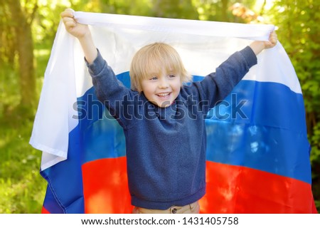 Portrait of cute little boy in public summer park with russian flag on background. Fans child supporting and cheering their national team. Day of independence. Pride and patriotism. #1431405758