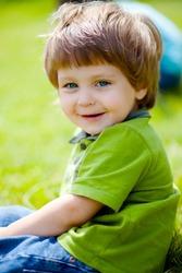 portrait of cute little boy sitting on the grass