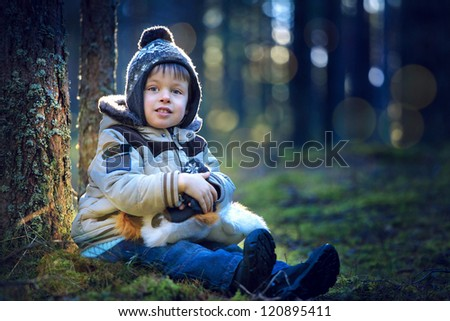 Portrait of cute little boy with toy in forest on cold winter day