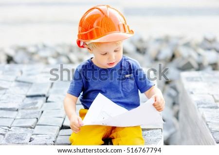 Portrait of cute little builder in hardhats reading construction drawing outdoors. Little boy\'s dream concept