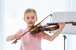 portrait of cute little child in pink dress playing violin at home