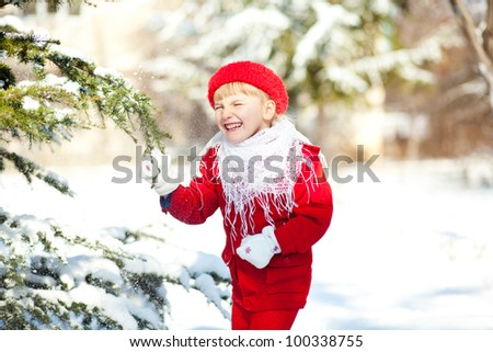 Portrait of cute little child playing with snow outdoors in winter