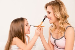 Portrait of cute little girl and her mom doing each other maquillage