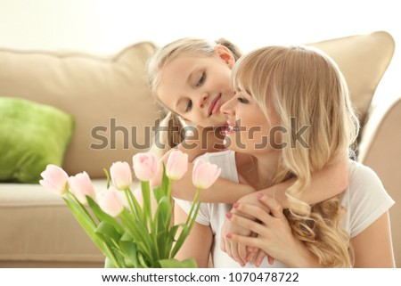 Portrait of cute little girl and her mother with tulip bouquet at home #1070478722