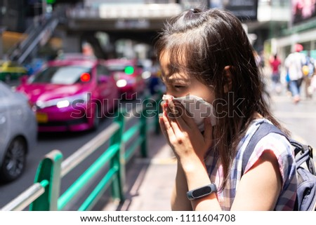 portrait of cute little girl blowing nose in paper handkerchief,Asian girl sneezing in a tissue in the city street concept of pollution,dust allergies #1111604708