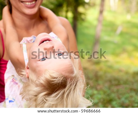 Portrait of cute little girl enjoying a summer day outdoors with her mom