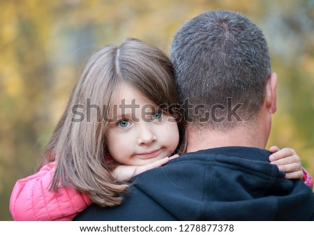 a35de29d Portrait of cute little girl held in father's arms. Happy loving family.  Father and · Mom hugs the child.