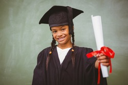 Portrait of cute little girl in graduation robe holding diploma