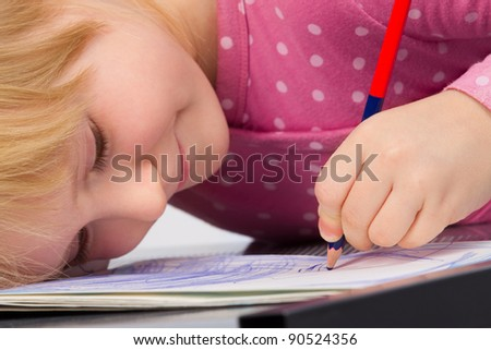 Portrait of cute little girl is drawing with pencil