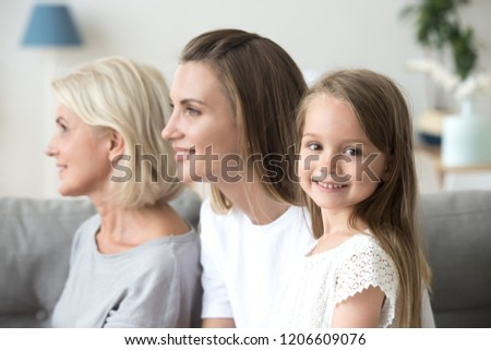 Portrait of cute little girl looking at camera smiling, mother and grandmother watch in distance imagining bright future for family, three generations of women in one picture, profile shot