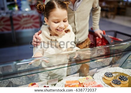 Portrait of cute little girl looking excited in bakery counter, choosing sweet pastry for dessert and smiling