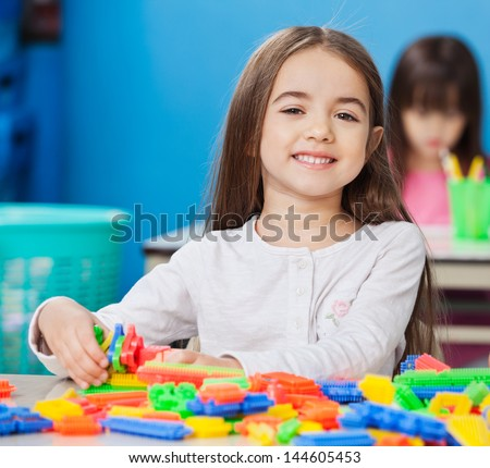 Portrait of cute little girl playing with construction blocks with friends in background at kindergarten
