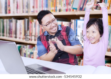 Portrait of cute little girl raising hands in the library while celebrating her success with teacher