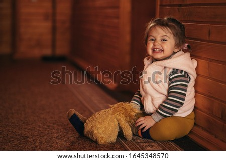 Portrait of cute little girl sits and leans on wooden wall in corridor, shows teeth, grimaces, makes faces. Small toddler sitting on the floor. Soft toy on child legs. Beautiful kid waiting in house