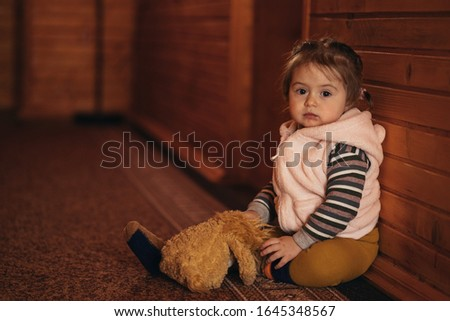 Portrait of cute little girl sits and leans on wooden wall in corridor. Small toddler sitting on the floor against wood plank wall. Soft toy on child legs. Braided hair. Beautiful kid waiting in house