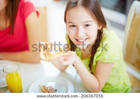 Portrait of cute little girl sitting by dinner table and eating pizza