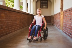 Portrait of cute little girl sitting in wheelchair in school corridor