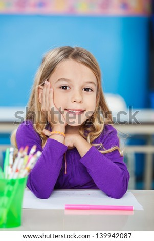 Portrait of cute little girl sitting with hand on chin at desk in kindergarten