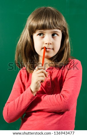 Portrait of cute little girl thinking in front of blackboard,Little girl thinking