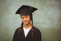 Portrait of cute little girl wearing graduation robe