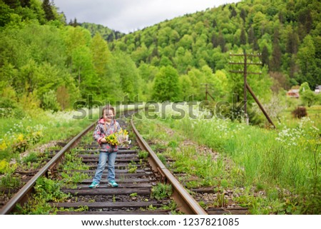 Portrait of cute little girl with bouquet on railway tracks