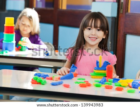 Portrait of cute little girl with construction block while friend playing in background at preschool