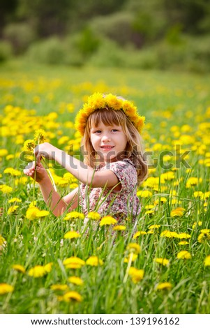 Portrait of cute little girl with dandelion wreath enjoying a summer day outdoors