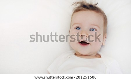portrait of cute little happy baby boy lying on soft white pillow, happy family concept