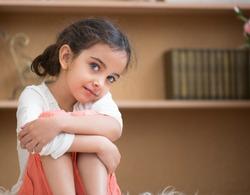 Portrait of cute little hispanic girl sitting on carpet at home