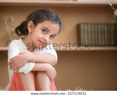 Portrait of cute little hispanic girl sitting on carpet at home