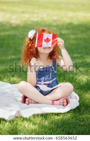Portrait of  cute little red-haired Caucasian girl child holding Canadian flag with red maple leaf, sitting on grass in park outside, celebrating Canada Day anniversary #658563652
