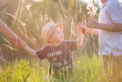 Portrait of cute little toddler boy in a straw hat holding his mother's  and brother's hands. Adorable child walking with his mom and sibling in the park on a sunny summer day. Family on sunset.