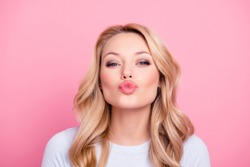 Portrait of cute lovely girl in casual outfit with modern hairdo sending blowing kiss with pout lips looking at camera  isolated on pink background. Affection feelings concept