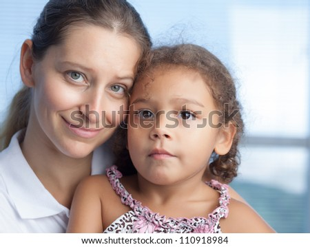 Portrait of cute mother and daughter looking at camera