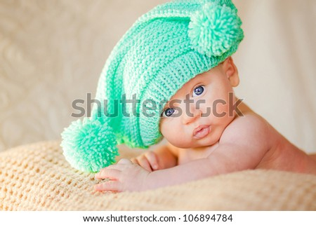 Portrait of cute newborn baby in a funny knitted hat