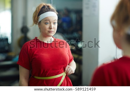 Portrait of cute obese woman standing against mirror in gym and measuring waist size with tape after workout, looking upset and confused