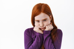 Portrait of cute redhead girl pouting, making coy sulking face and look gloomy from under forehead, standing upset against white background