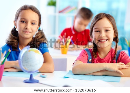 Portrait of cute school girls sitting at their desk
