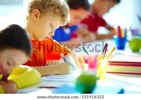 Portrait of cute schoolboy drawing at workplace among his classmates