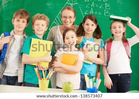 Portrait of cute schoolchildren looking at camera with their teacher among them