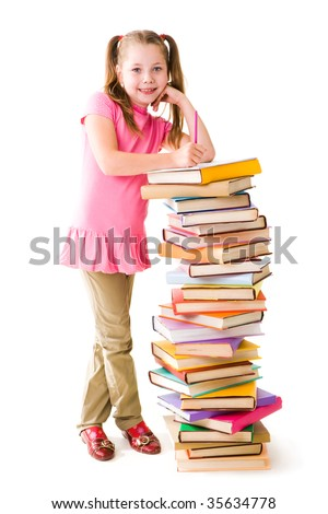 Portrait of cute schoolgirl standing by stack of books and looking at camera
