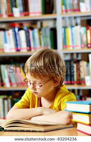 Portrait of cute schoolkid reading in the library