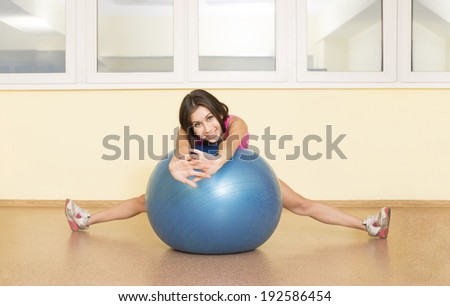 Portrait of cute sexy fitness girl in gym dress based on blue rubber ball near yellow wall and window Beautiful latin hispanic woman sitting on the splits