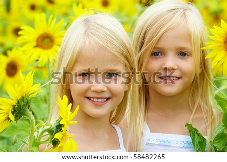 Portrait of cute sisters in sunflower field