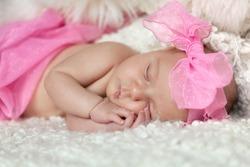 Portrait of cute sleeping newborn girl on white background, indoor