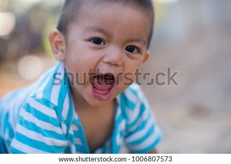 Portrait of cute small boy looking camera with happy and smiling on a nature background #1006807573
