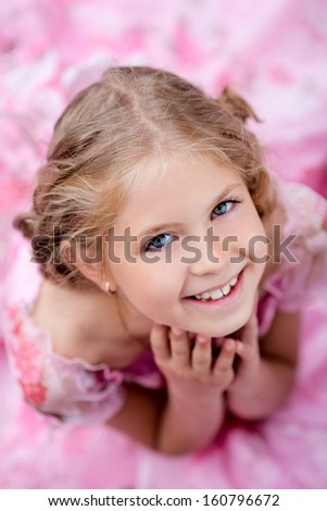 Portrait of cute smiling little girl in pink dress