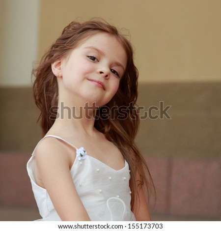 Portrait of cute smiling little girl with long hair in a beautiful dress is sitting on the steps outdoors - stock photo